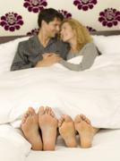 Young couple lying in bed, close-up of feet Stock Photos