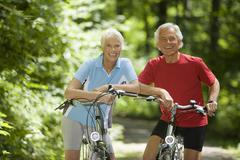 Stock Photo of Senior couple with bikes, smiling, portrait