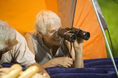 Senior couple camping, woman with field glasses, portrait Stock Photos