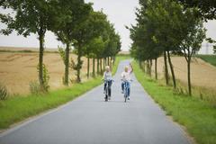 Senior couple biking on country road Stock Photos