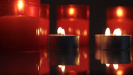 Red candles burning and shimmering in the dark rotating before camera. Stock Footage