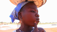 A woman sells trinkets and other good along the roadside in Mali, Africa. Stock Footage