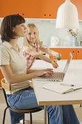 Stock Photo of Mother and daughter (8-9) in the kitchen, mother using laptop