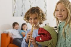 Boy (6-7) and girl (8-9), playing recorder, portrait - stock photo