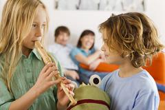 Boy (6-7) and girl (8-9), playing recorder - stock photo
