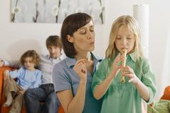Mother and daughter (8-9), playing recorder - stock photo