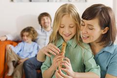 Mother and daughter (8-9), playing recorder Stock Photos