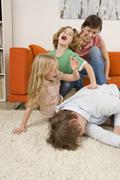 Family in living room, laughing Stock Photos