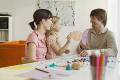 Parents playing with daughter (8-9) - stock photo