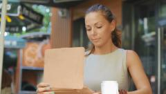Young business woman sits at a table at a fast food restaurant Stock Footage