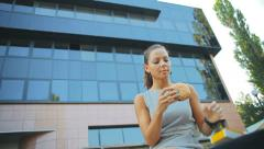 Young business woman sitting near the office building and eating a burger Stock Footage