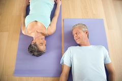 Mature couple on gymnastic mat, smiling, portrait Stock Photos