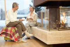 Mature couple sitting in front of fireplace - stock photo