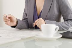 Businesswoman taking notes, drinking coffee, mid section Stock Photos