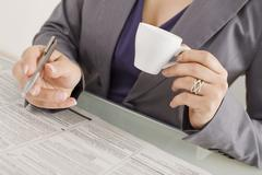 Businesswoman taking notes,holding a cup of coffee, mid section - stock photo