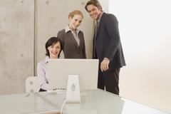 Three business people using a computer Stock Photos