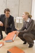 Business people gathering folders from floor Stock Photos