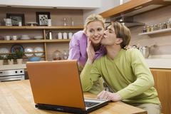 Young couple in kitchen, using laptop, portrait - stock photo