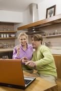Young couple in kitchen, watching laptop, portrait - stock photo