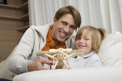 Father and son (8-9) playing with model aeroplane, portrait Stock Photos