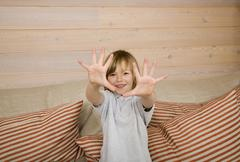 Stock Photo of Boy (8-9) showing all ten fingers at camera, smiling, portrait