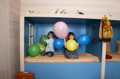 Boy (8-9) and girl (6-7) playing with balloons, smiling, portrait - stock photo