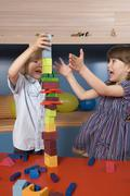 Boy (8-9) and girl (6-7) playing building bricks, portrait - stock photo