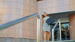 Young business woman coming out of an office building, she is very happy - stock footage