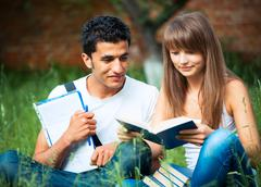 Two students guy and girl studying in park on grass with book Stock Photos