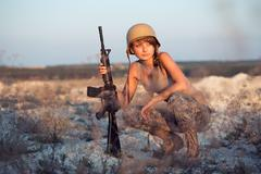 Young beautiful female soldier dressed in a camouflage with a rifle Stock Photos