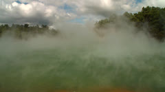Steam rises off a geothermal lake in New Zealand's Rotorua region. - stock footage