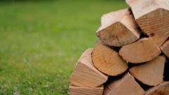 Dolly shot of Wood pile infront of green grass Stock Footage