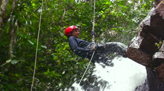 A man rapels with a rope over a waterfall in Costa Rica. Stock Footage