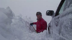 A man digs his car out of a snowstorm in winter. Stock Footage