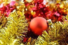 christmas balls over shiny red and yellow  tinsel - stock photo