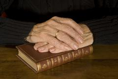 old hands resting at antique bible - stock photo