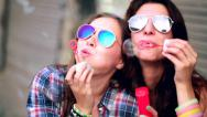 Two friends in hipster outfit having fun blowing bubbles in city Stock Footage