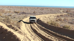 An old jeep passes on a deeply rutted road near the Aral Sea Uzbekistan. Stock Footage