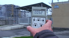 A person holds up a Geiger counter to read radiation near the Chernobyl nuclear Stock Footage