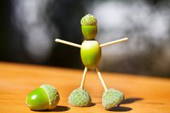 Little man made of green acorns on wood Stock Photos