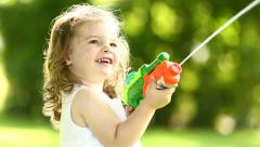 Kid cheerfully splashing water with squirt gun Stock Footage