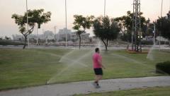 Man walking under watering jets Stock Footage