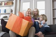 Grandmother and grandchildren (8-9) with gift Stock Photos