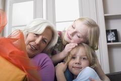 Grandmother and grandchildren (8-9) with gift - stock photo