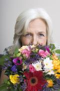 Senior woman holding bunch of flowers, portrait - stock photo