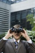 Germany, Baden-Wurttemberg, Stuttgart, Businessman looking through field glass - stock photo