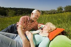 Germany, Baden Wurttemberg, Tubingen,  Senior couple relaxing on meadow Stock Photos