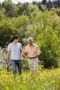 Germany, Baden Wurttemberg, Tubingen, Mature father and adult son walking - stock photo