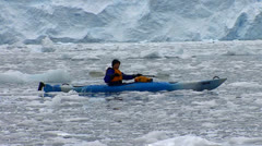 A man paddles a kayak in the Arctic or Antarctic with many icebergs nearby. - stock footage