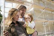 Stock Photo of Young family in front of New Home Under Construction
